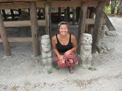 Becky crouched next to two statues at Parulubalangan