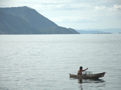 A fisherman prepares his nets; Lake Toba