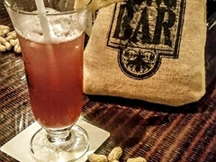 Singapore Sling (a gin based pineapple juice cocktail) coupled with peanuts - a Long Bar institution