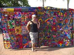 Becky strikes a pose next to two colorful bed spreads (starting price was $400 which quickly dropped when we weren't interested); Puntarenas