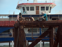 Workers strap themselves to a platform by the pier in Puntarenas