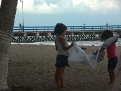 Two young girls work together to spread a tarp on the beach; Puntarenas