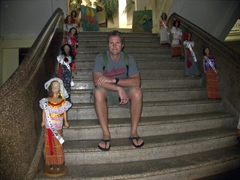 Robby strikes a pose next to dolls representing Tapachula and neighboring towns; Casa de Cultura