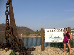 "Becky strikes a pose next to the ""Welcome to Huatulco"" signpost at the cruise ship terminal in Santa Cruz"