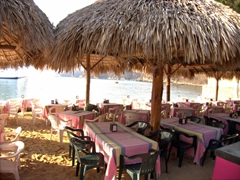 Beach side restaurants compete for your business; Santa Cruz Bay in Huatulco