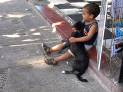 A young boy hugs his dog outside a store that does not permit pets inside; Puerto Vallarta