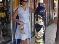 Becky next to a massive tequila bottle