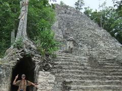 Robby standing beneath the roots of a tree at Coba
