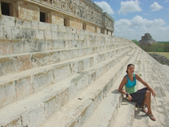 Becky sits on the staircase leading up to the Governor's palace with the Piramide del Adivino in the background