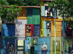 Street billboards give us a sampling of what to expect at colorful Caminito; Buenos Aires