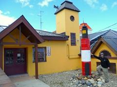 Robby strikes a pose next to a miniature lighthouse; Ushuaia