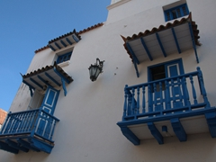 Blue balconies stand out against a white washed building