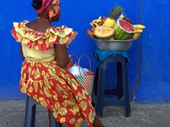A weary Palenquera (traditionally dressed fruit vendor) rests her tired feet