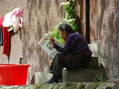 An elderly lady reading a newspaper; El Barranco