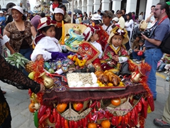 Young girls atop their float with offerings of cuy (roasted guinea pig) and cookies