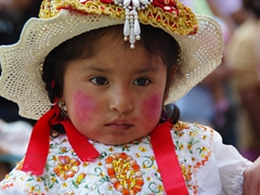 Young girl with rosy red cheeks gazes off in the distance; Pase del Niño Viajero