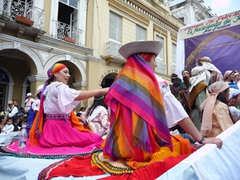 Colorfully clad ladies wave to the crowd; Pase del Niño Viajero