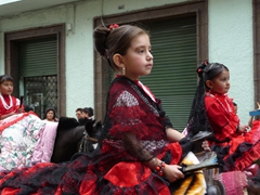 Girls are dressed in their finest atop horses for the Pase del Niño Viajero