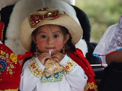 Young girl getting ready to tear open her bag of animal crackers; Pase del Niño Viajero