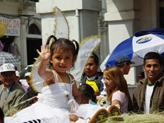 A happy little angel waves to the crowd; Pase del Niño Viajero