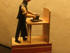 Wooden carving of a man making a panama hat; Museo del Monasterio de las Conceptas