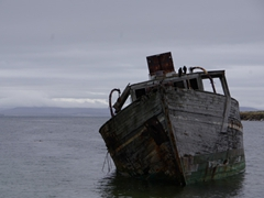 A decrepit wooden boat lies near the dry landing dock at New Island