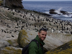 Robby smiling broadly at the amazing sight of hundreds of Rockhopper penguins in a gully leading to the sea; New Island Settlement