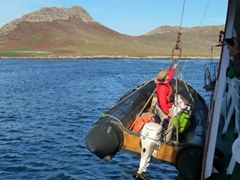 Hugh Rose in one of the zodiacs being lowered; Steeple Jason Island in the background