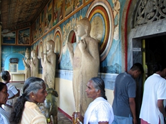 Pilgrims mingle among the Buddha statues outside the temple of Ruwanweliseya Dagoba, Anuradhapura