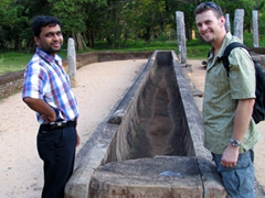 "Sri and Robby stand before the ancient ""feeding trough"" where rice was donated to over 12,000 monks; Anuradhapura"