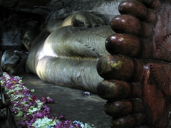 A 14 meter rock hewn statue of Buddha reclines in the Cave of the Divine King, Dambulla Cave Temple