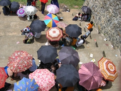 Locals seek refuge from the scorching sun beneath their umbrellas