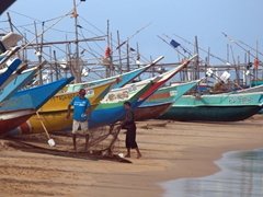 Fishermen untangling a net against the backdrop of colorful fishing vessels; Dodanduwa Beach