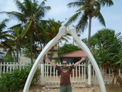 Robby poses beneath a set of whale bones; Mount Lavinia beach