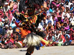 Close up of a dancer at the Paro Tsechu; notice the huge crowd gathered for this popular event!