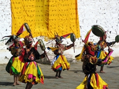 Dance of the Drum from Dramitse (These monks are wearing yellow knee length skirts and beating on their drums with a drumstick)