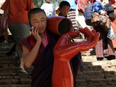 Young monk carrying huge statue hands while chatting on a cell phone...not an everyday sight!