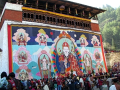 The huge thangka is quickly rolled up as sunlight appears on the last day of Paro Tsechu