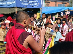 Parting the crowd with his horn to make way for the massive Thangka