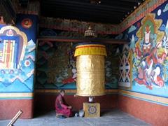 Monk seated next to huge prayer wheel; Punakha Dzong