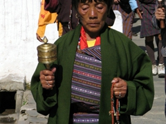 Deep in thought; Thimphu woman spinning her prayer wheel