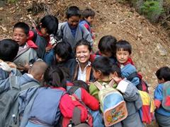 School children swarm around Becky to view their photo, small village near Thimpu