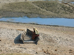 A Nepalese woman rests on an decrepit boat; Chitwan National Park
