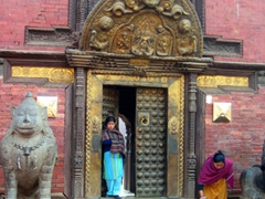 A woman sweeps the main entrance to a temple in Patan Durbar Square