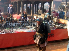 A Nepalese vendor wanders through Patan Durbar Square in search of a place to sell his goods
