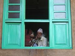 An elderly Nepalese man smokes a wooden hookah; Patan