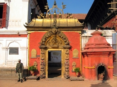 A guard stands beside the Golden Gate in Bhaktapur Durbar Square. The gate is the main entrance to the courtyard containing the Palace of 55 Windows