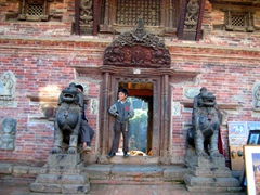 A boy straddles the entrance way to one of Bhaktapur's numerous temples