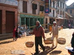 Two men transporting goods through Bhaktapur