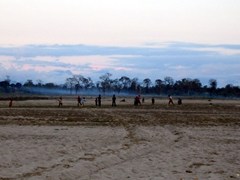 Children playing soccer on the sandy field at dusk; Chitwan National Park